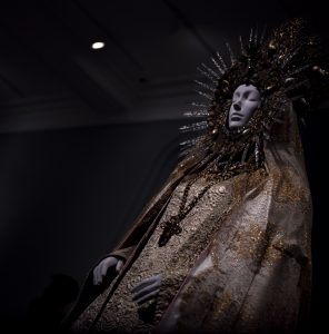 "Yves Saint Laurent. Statuary Vestment for the Virgin of El Rocio, ca. 1985. Gold silk brocade with white and pink silk satin, gold silk and metal Chantilly lace, gold metal with polychrome crystals and pearls. ""Heavenly Bodies: Fashion and the Catholic Imagination"". ©Kristina Nazarevskaia for galleryIntell"